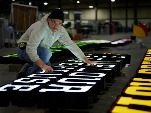 Male sign manufacturer kneeling on ground to test sign lighting