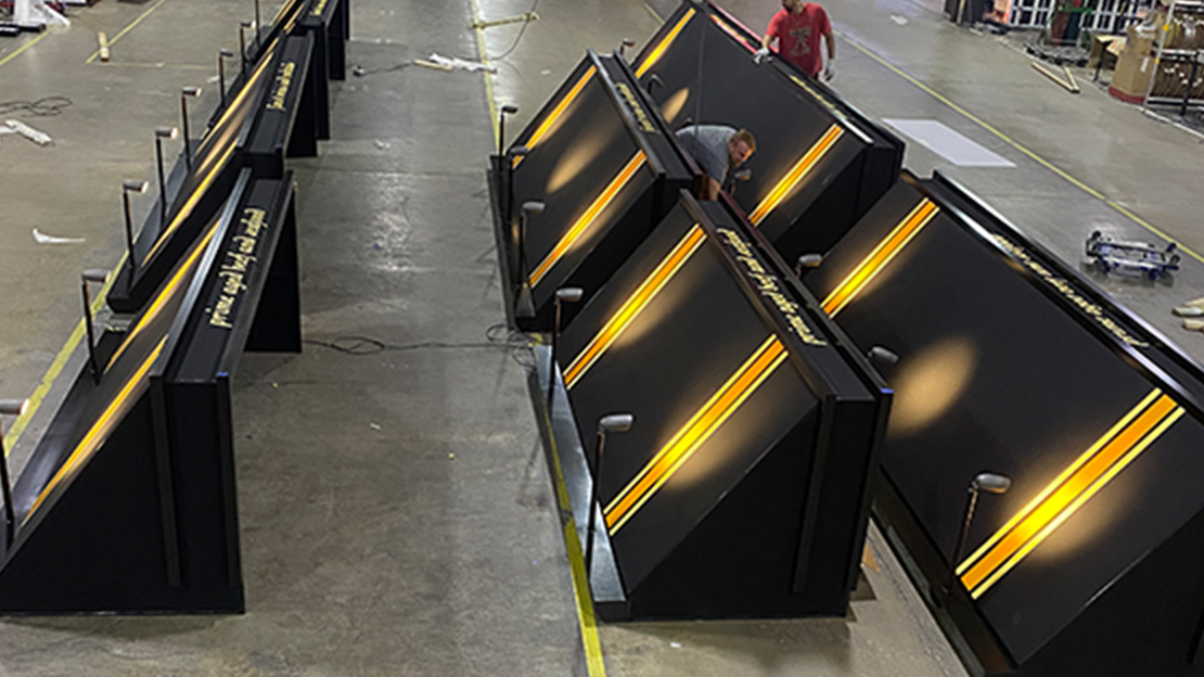 Multiple of the same black awnings with spotlights laying on factory floor getting ready for shipment