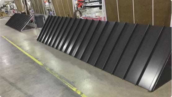 Painted black metal paneling laying against wall in workshop