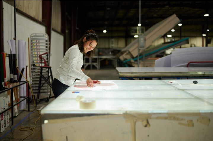 Women cutting excess paper from printed paper sign