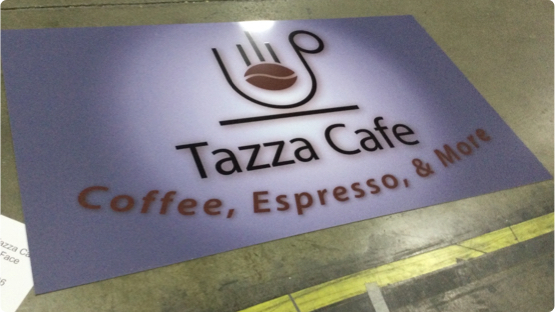 Tazza Café Logo printed on paper sign laying on factory floor
