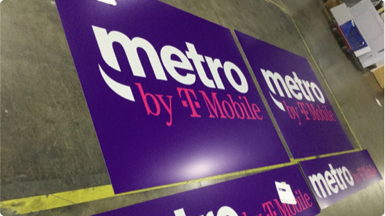 Metro by Tmobile Logo printed on paper sign laying on factory floor