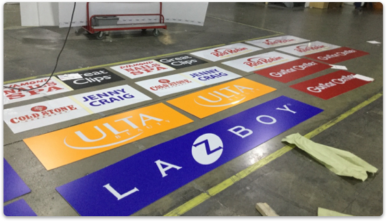 Various company logos printed on paper laying across factory floor