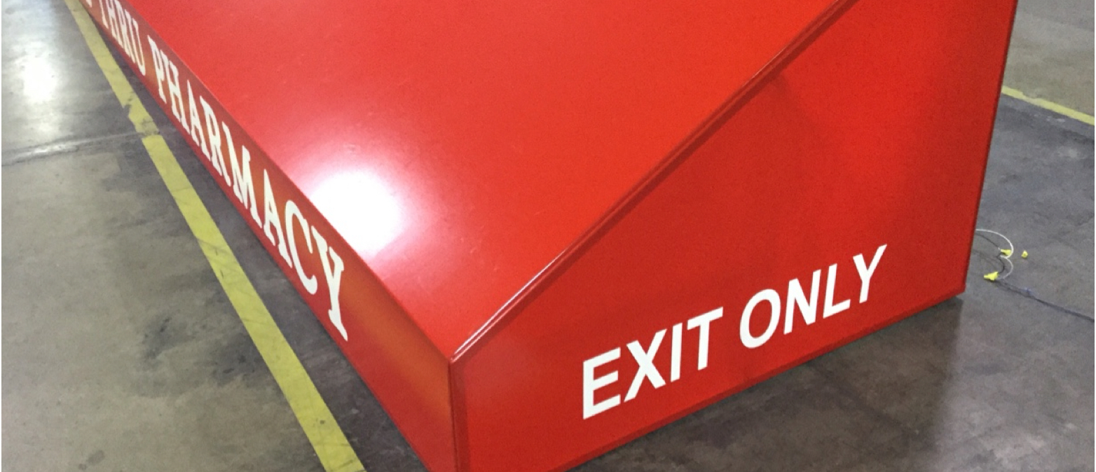 Red awning with Exit only printed on side laying on factory floor getting ready for shipment