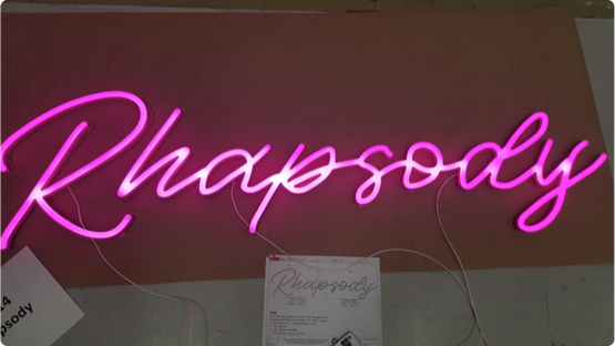 Lit up pink LED light that reads Rhapsody laying on factory floor getting ready for shipment