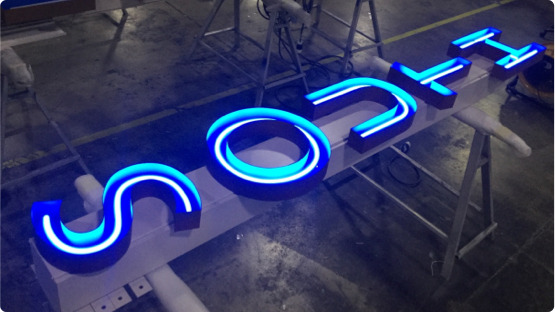 Lit up blue LED light that reads South laying on factory floor getting ready for shipment