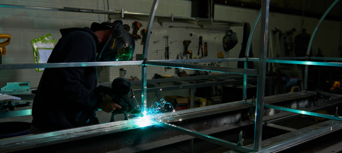 Male welding metal together to create building sign structure with sparks flying