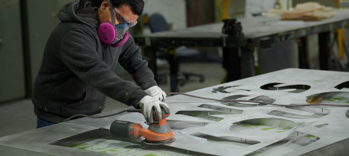 Male wearing face masks sanding metal sign wearing white gloves