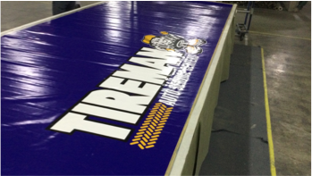 Tireman building sign laying on factory floor getting ready for shipment