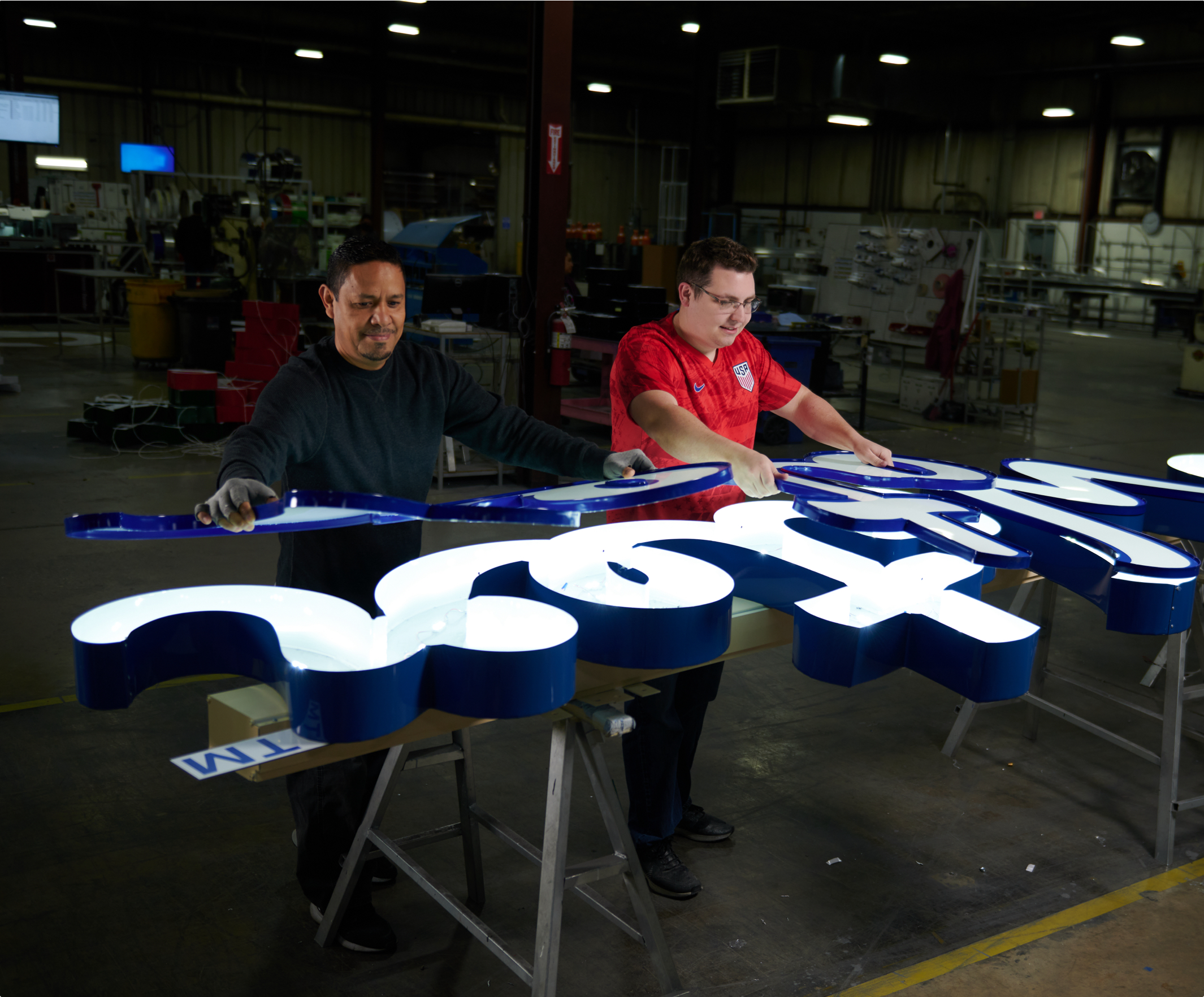 Male Sign Manufacturers adding final touches to client's building sign in Awning Innovations workshop